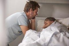 Отец говоря доброй ночи к дочери на времени ложиться спать стоковые фото
