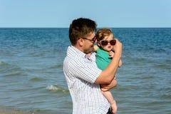Отец держит маленькую дочь на его плечах в солнечных очках стоковое изображение rf
