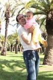 отец дочи поднимая меньший парк Стоковое фото RF