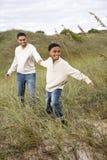 отец дюн мальчика афроамериканца вытягивая песок стоковые фотографии rf
