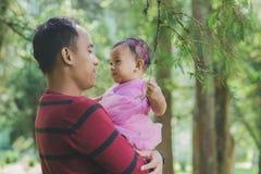 Отец держит маленькую дочь в ее оружиях среди деревьев стоковое изображение rf