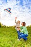 Отец держит ребенк пока наблюдающ змея летая Стоковая Фотография