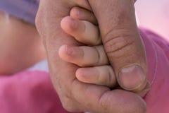 Отец держит руку ее newborn младенца, влюбленность концепции Стоковое Изображение RF