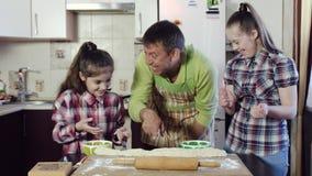 Отец жизнерадостно показывает его дочерям как сделать тесто сток-видео