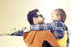 Отец заботя его сын к ландшафтам зимы wanderfull, растя Стоковые Изображения