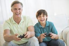 Отец играя видеоигру совместно дома стоковые изображения