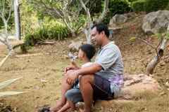 Отец играя мыло пузыря с его сыном Стоковые Фото