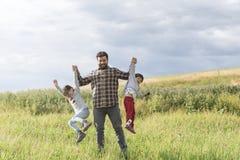 Отец играя поднимающ его дочь и сына стоковое изображение rf