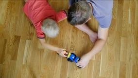 Отец играя с его сыном, взгляд сверху скрепляет болтами гайки семьи принципиальной схемы состава акции видеоматериалы