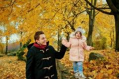 Отец идет с дочерью ребенка в парке осенью Стоковые Изображения