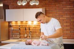 Отец изменяет ворсистый к его ребёнку стоковое фото rf