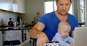Отец используя ноутбук пока ребенок играя с игрушкой 4k сток-видео