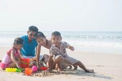 Отец и дети играя песок на пляже стоковое фото rf