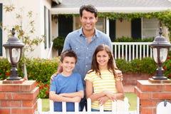 Отец и дети стоя внешний дом стоковое фото rf