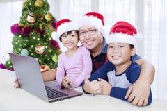 Отец и дети с компьтер-книжкой на времени рождества Стоковые Изображения