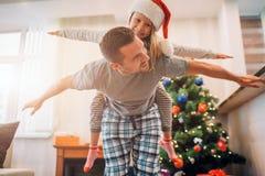 Отец и дочь играя в комнате Он едет она на его назад Они держат руки в сторону тела Молодой человек смотрит девушку стоковое фото