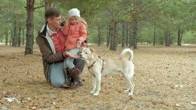 Отец и дочь играя в парке влюбленн в собака сток-видео