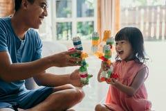Отец и дочь играя головоломку стоковое фото