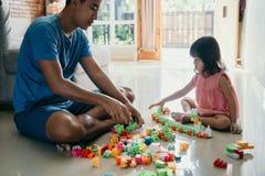Отец и дочь играя головоломку стоковое фото rf