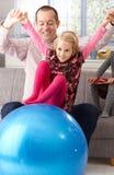 Отец и дочь играя с шариком пригонки дома Стоковые Изображения RF