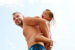 Отец и дочь имея потеху совместно на пляже стоковое фото