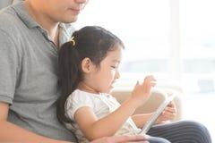 Отец и дочь используя цифровую таблетку Стоковое Изображение