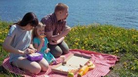 Отец и дочь матери едят пиццу морем побережья видеоматериал