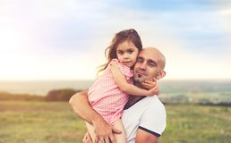 Отец и дочь обнимая на заходе солнца лета стоковые фото