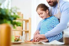 Отец и дочь подготавливая здоровый обедающий стоковые изображения rf