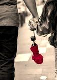 Отец и дочь рука об руку с красным зонтиком стоковая фотография