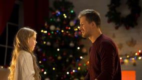 Отец и дочь сидя около рождественской елки, празднуя праздники совместно стоковое фото