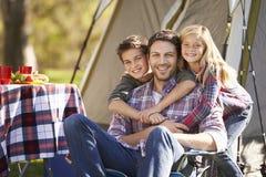 Отец и дети наслаждаясь располагаясь лагерем праздником Стоковое Изображение