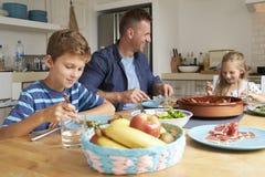 Отец и дети дома в есть еду совместно Стоковое Изображение RF