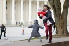 Отец и 2 дет бежать и смеясь над Стоковая Фотография