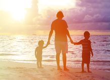 Отец и 2 дет идя на заход солнца Стоковое Изображение