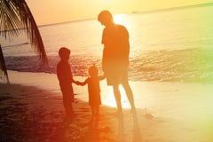 Отец и 2 дет идя на заход солнца Стоковое Фото