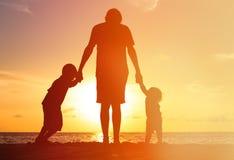 Отец и 2 дет идя на заход солнца Стоковая Фотография
