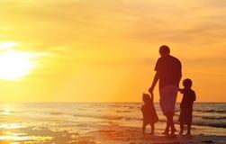 Отец и 2 дет идя на заход солнца Стоковые Фото