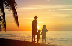 Отец и 2 дет идя на заход солнца Стоковое фото RF