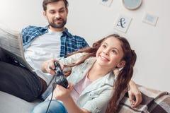 Отец и маленькая дочь дома сидя девушка играя конец-вверх пока газета чтения отца стоковые изображения