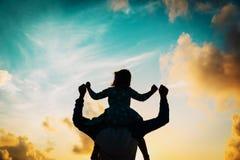 Отец и маленькая дочь на плечах играют на заходе солнца Стоковая Фотография