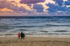 Отец и маленький ребенок наблюдая заход солнца на Балтийском море с c стоковое фото rf
