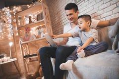 Отец и маленький сын смотрят кино на компьтер-книжке на ноче дома стоковая фотография