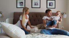 Отец и мать играя с мальчиком 2 года лежа в кровати акции видеоматериалы