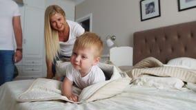 Отец и мать играя с мальчиком 2 года лежа в кровати видеоматериал