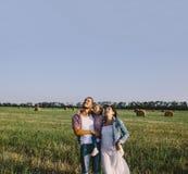 Отец и мать обнимают ее маленькую дочь внешнюю в поле Стоковое Изображение