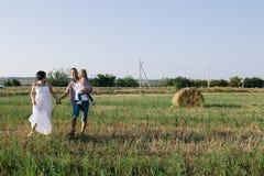 Отец и мать обнимают ее маленькую дочь внешнюю в поле Стоковое Изображение RF