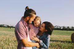 Отец и мать обнимают ее маленькую дочь outdoors в поле Стоковое Изображение RF
