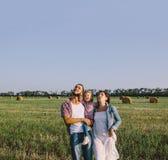 Отец и мать обнимают маленькую дочь outdoors в поле Стоковая Фотография