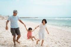 Отец и мать отбрасывая маленькую девочку на пляже стоковые изображения